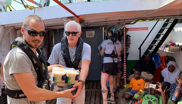 US actor Richard Gere helps to carry supplies aboard Open Arms rescue boat