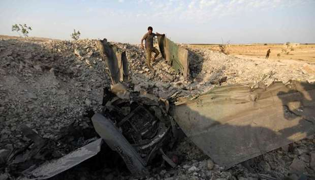 A rebel fighter stands near the remains of a downed regime warplane near the jihadist-held town of K