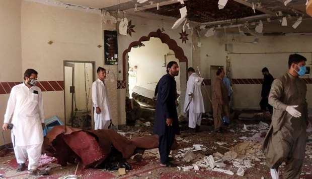Members of a bomb disposal unit survey the site after a blast at a mosque in Kuchlak, in the outskir