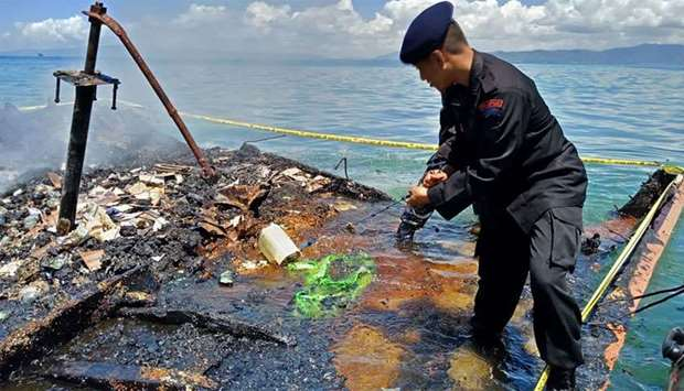 Indonesian policeman inspecting the charred remains of a ferry that caught fire near Kendari, off In