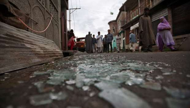 Kashmiris walk past broken window glass after clashes between protesters and the security forces on