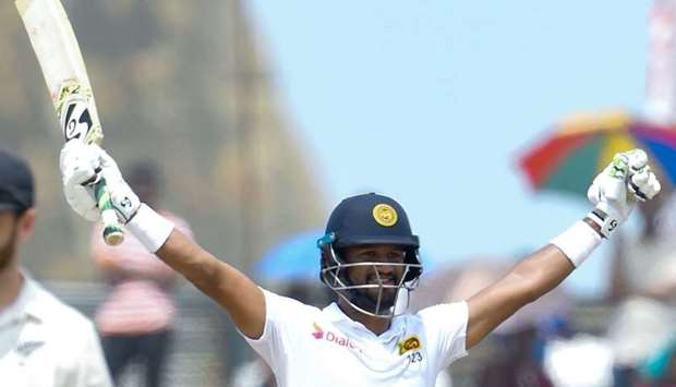 Sri Lanka's cricket team captain Dimuth Karunaratne (R) celebrates after scoring a century (100 runs