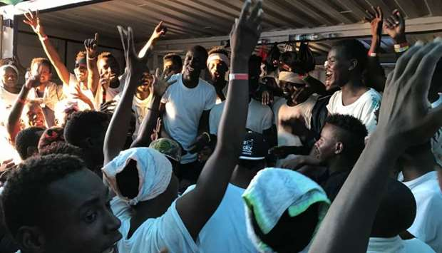 Rescued migrants gesture as they gather on deck of the 'Ocean Viking' rescue ship, operated by Frenc