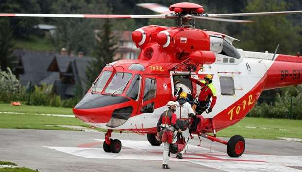 Mountain rescue team (TOPR) members board a helicopter in Zakopane, Poland to join the search operat