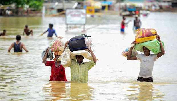 Flood-affected residents of a low lying area on the banks of the Ganges river move their belongings