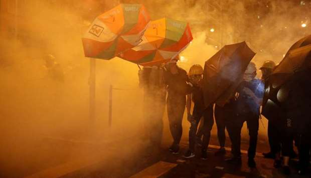 Pro-democracy protesters shield themselves with umbrellas in tear gas as they clash with police in H