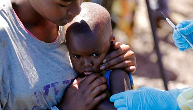 A child reacts as a health worker injects her with the Ebola vaccine, in Goma, Democratic Republic o