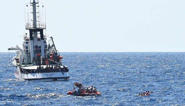 Migrants swim after jumping off the Spanish rescue ship Open Arms, close to the Italian shore in Lam