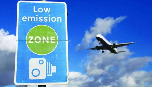 An aircraft operated by British Airways passes a low emission zone sign as it prepares to land at He