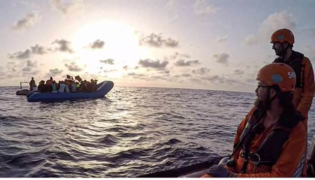 Members of the German migrant rescue charity NGO Sea-Eye helping people to get off from an overloade