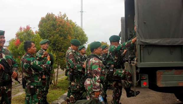 Indonesian soldiers get on to the vehicle as they arrive at Domine Eduard Osok Airport to be deploye