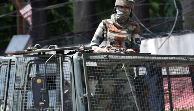 In this file photo taken on August 18, 2019, an Indian army soldier stands alert in a truck while tr