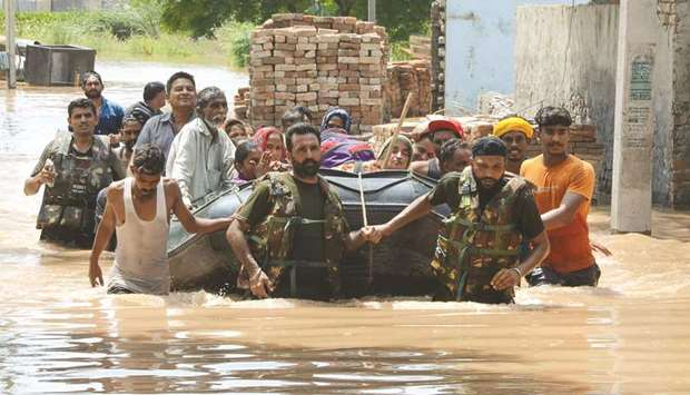 Army personnel rescue residents in a rubber boat following flooding in Kang Khurd, some 40km from Ka