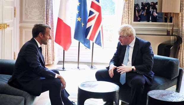 French President Emmanuel Macron and British Prime Minister Boris Johnson speak during a meeting at