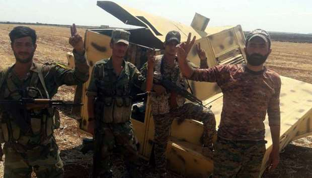Syrian army soldiers gesture as they pose for a picture in Idlib countryside, Syria in this handout