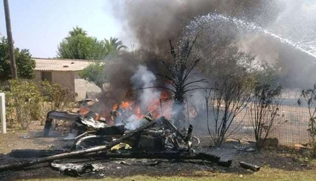 A man sprays water at wreckage on fire after a collision between a helicopter and a light plane that