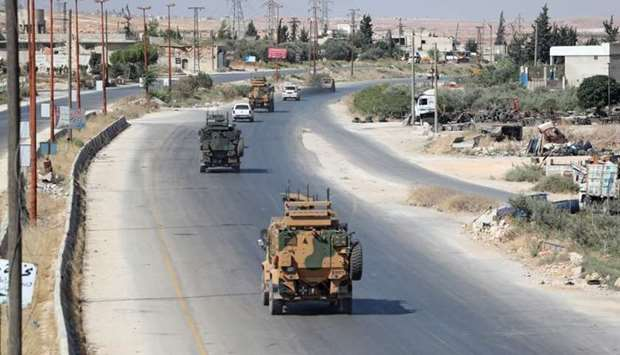 Turkish military vehicles drive down a road in Syria's northern province of Idlib on August 26, 2019
