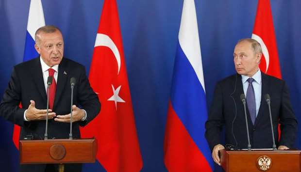 Turkish President Recep Tayyip Erdogan (L) speaks as Russian President Vladimir Putin (R) looks on d