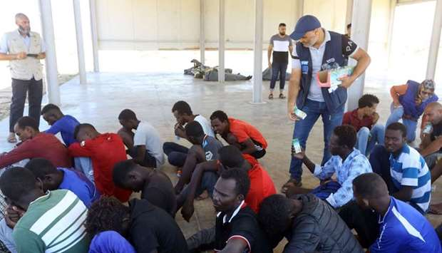 Rescued migrants receive food aid at a coast guard point in Khoms, some 100 kilometres from the Liby