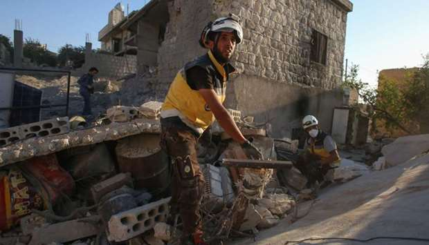 Members of the Syrian Civil Defence (White Helmets) look for survivors under the rubble of a buildin