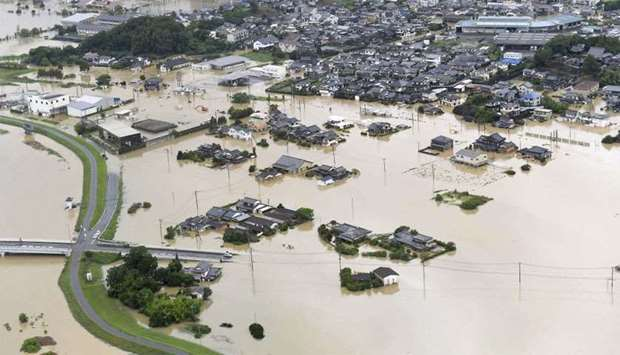 An aerial view shows submerged houses and facilities at a flooded area in Takeo, Japan
