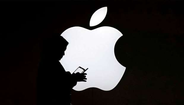 A woman looks at the screen of her mobile phone in front of an Apple logo