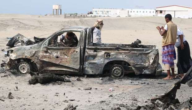 Yemeni fighters inspect burnt out armoured vehicles reportedly belonging to pro-government troops fo
