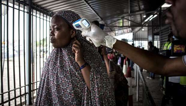 In this file photo taken on July 16, 2019 in Goma, a woman gets her temperature measured at an Ebola