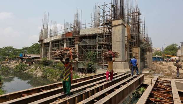 Women carry firewood on iron beams laid over a canal next to the construction site of a metro rail s