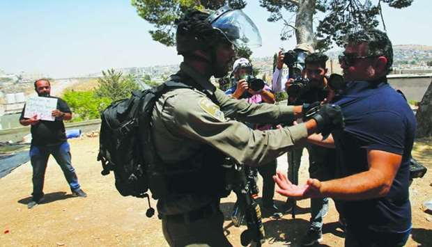 An Israeli border policeman grabs a Palestinian demonstrator during a protest against the Israeli de