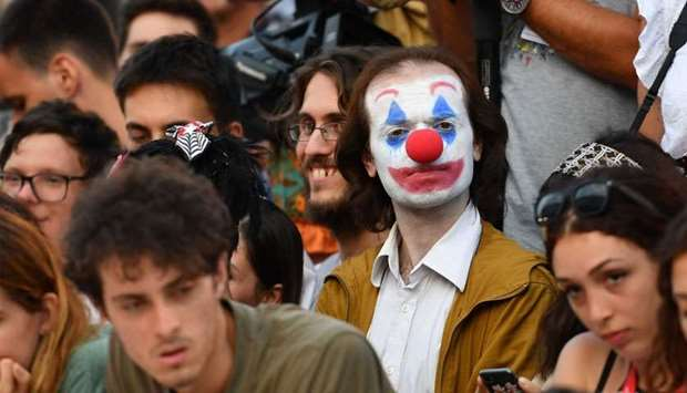 A festival goer wearing a clown make up waits in the public for guest's arrivals, prior to the scree