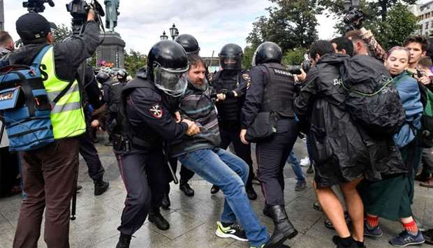 Riot police officers detain a participant of an unsanctioned rally urging fair elections at Moscow's