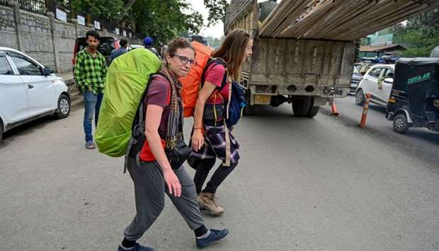 Tourists from Belgium walk on a road as they are going to leave Kashmir in Srinagar