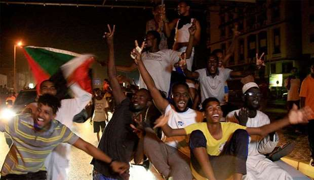Sudanese demonstraters wave their national flag as they celebrate in Khartoum early on Thursday, aft