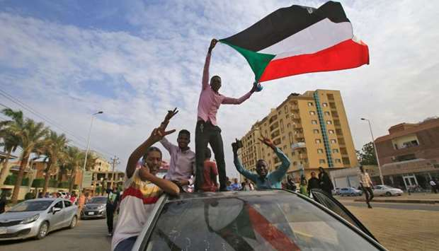 Sudanese protesters wave their national flag during a demonstration