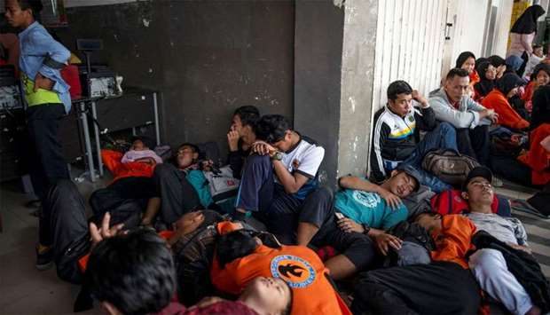 Commuter train passengers rest as they wait to travel to Jakarta outside a station, closed due to a