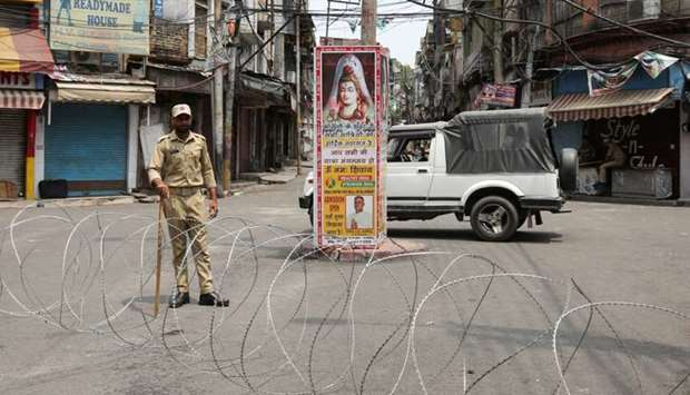 An Indian security personnel stands guard along a deserted street during restrictions in Jammu