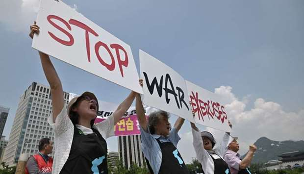"""Anti-war activists hold placards reading """"Stop War Exercises,"""" during a rally against planned South"""