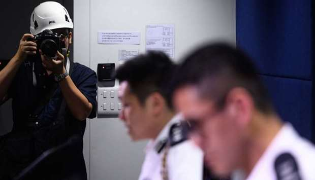 A photographer, wearing a protective helmet during a police press conference- Hong Kong