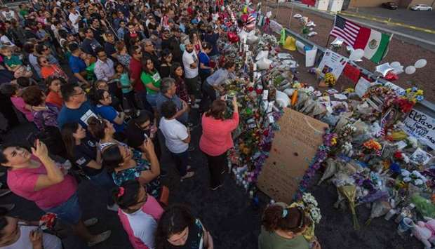 People pray and pay their respects at the makeshift memorial for victims of the shooting that left a