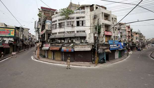 Indian policemen stand guard in a deserted street during restrictions in Jammu