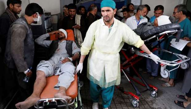 Men carry injured men to a hospital after a blast in Kabul