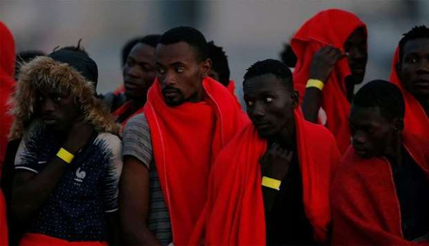 Migrants, intercepted off the coast in the Mediterranean Sea, wait to disembark from a rescue boat a