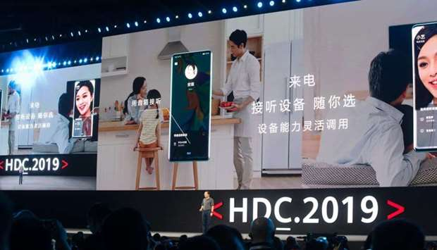 Richard Yu (bottom C), head of Huawei's consumer business, is seen in front of a giant screen as he