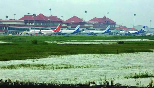 Airplanes are pictured as they are parked next to flood waters on the tarmac of the Cochin Internati