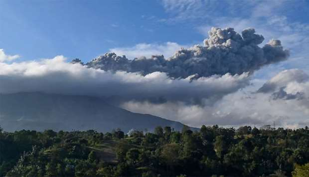 Sinabung volcano spews ash during its second eruption toward dusk as seen from Karo district, North