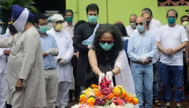Wife of deceased Air India pilot Deepak Sathe places flowers on his coffin during his funeral in Mum