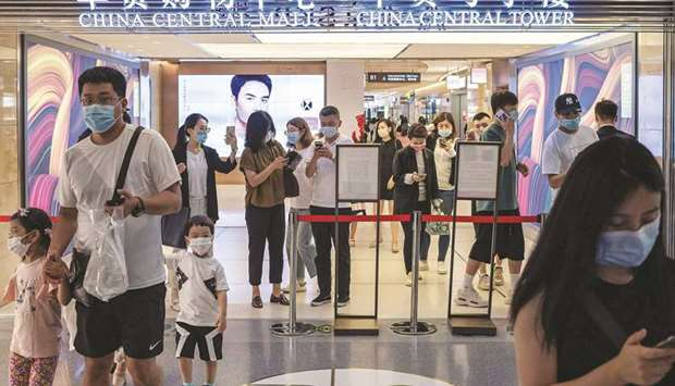 People show their health codes on their smartphones at the entrance of a mall in Beijing. China's re
