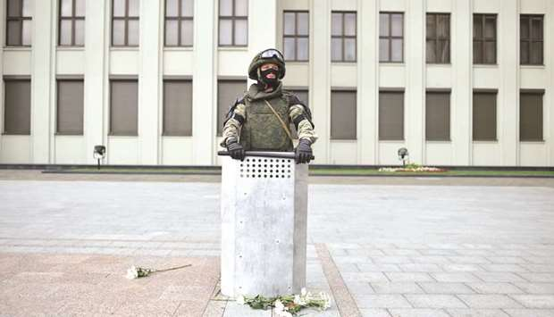 A Belarus law enforcement officer, with flowers left by protesters at his feet, stands guard in fron