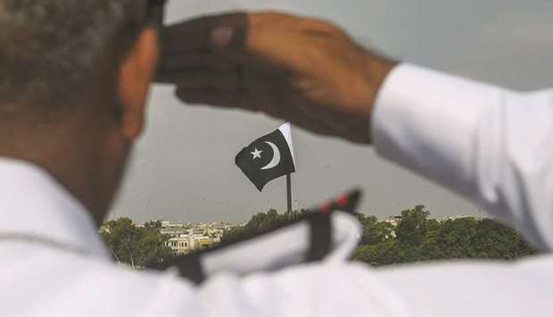 A Pakistan Navy officer salutes at the mausoleum of founder Mohamed Ali Jinnah during the Independen
